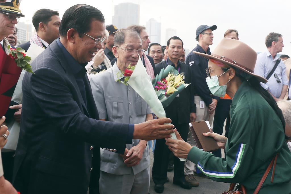 14日、カンボジア南部シアヌークビル港に到着したクルーズ船「ウエステルダム」から下船する乗客を出迎えるカンボジアのフン・セン首相(左)(AP)