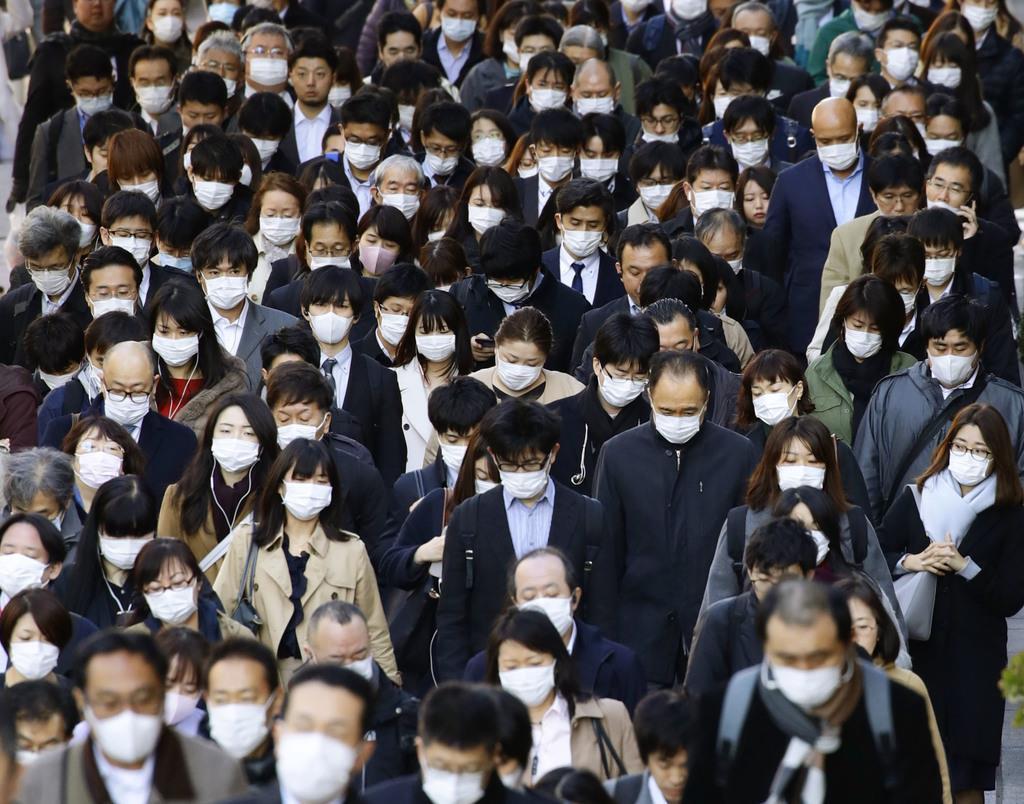 マスク姿で通勤する大勢の人たち=12日、東京都中央区