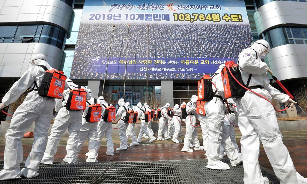 韓国南東部大邱の新天地イエス教会施設前で、防護服を着用して消毒剤を散布する兵士ら =(AP)