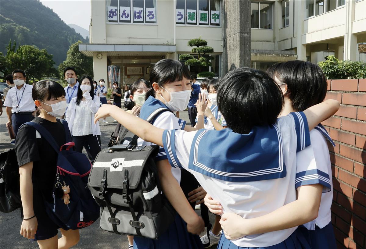1カ月ぶりに再開した球磨中に登校し、抱き合って再会を喜ぶ生徒たち=3日午前、熊本県球磨村