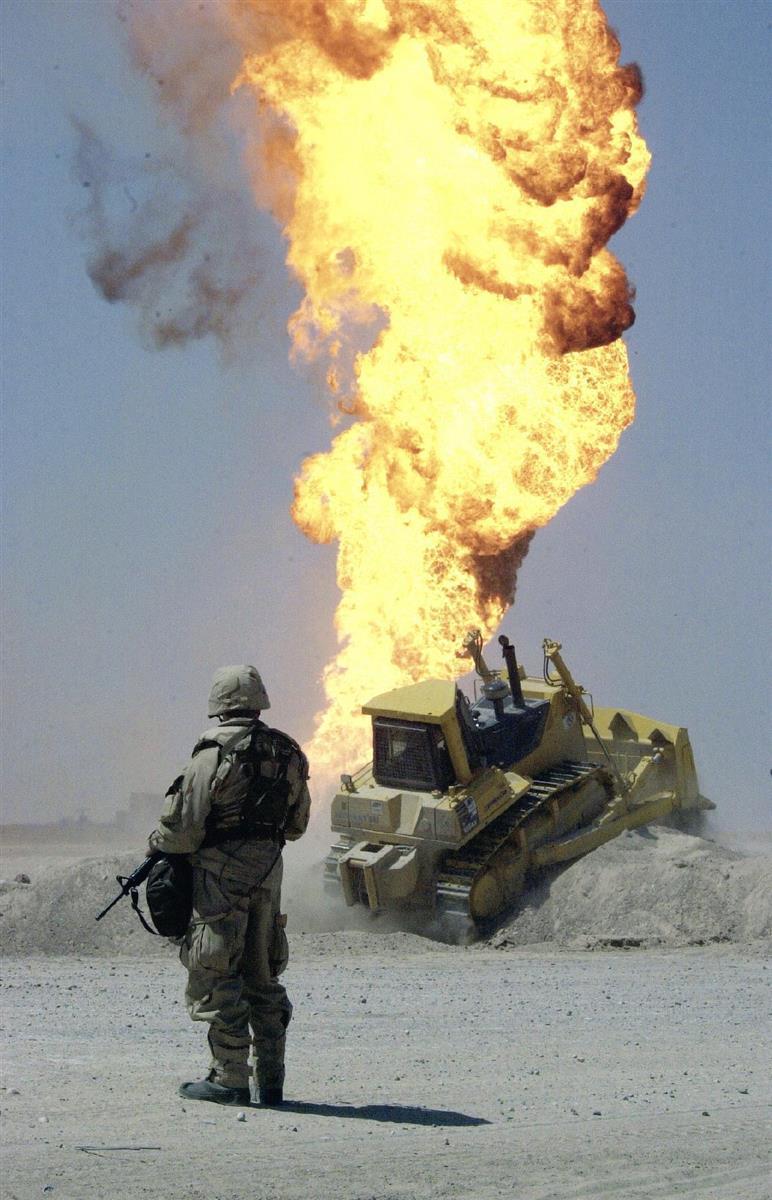 2003年4月、イラク南部有数の油田地帯ルメイラで燃え上がる油井を警備する米兵。イラク戦争の初期に、後退するイラク軍が火を放ったと伝えられた(AP)