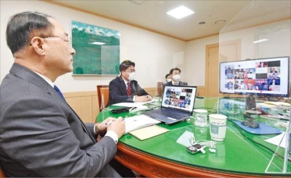 <G20首脳会議財務長官と画像会議>韓国の洪楠基(ホン・ナムギ)副首相兼企画財政部長官(左)が先月26日、政府ソウル庁舎で主要20カ国・地域(G20)財務相と画像会議を行っている。今年初めて開かれたG20財務相・中央銀行総裁会議は非対面で開催された。[写真 韓国企画財政部]