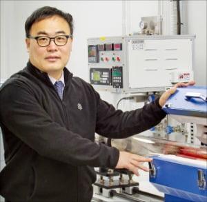 グラフェンスクエアのホン・ビョンヒ代表がグラフェン素材生産装備を紹介している。[写真 グラフェンスクエア]