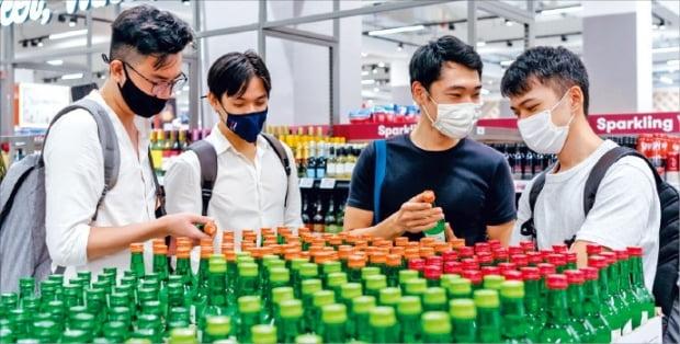 シンガポールの流通チェーン店フェアプライスで消費者がフルーツ味の焼酎をチェックしている。[写真 ハイト真露]